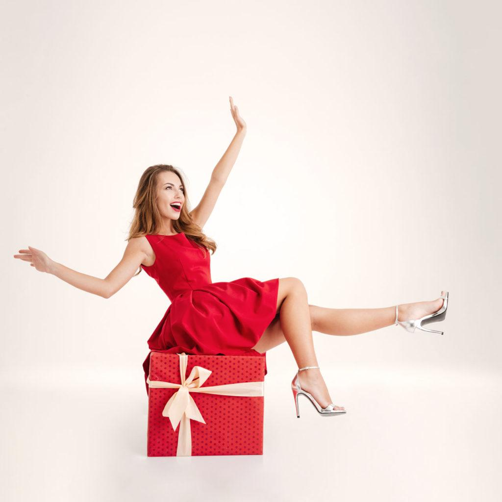 Woman in red fancy dress sitting on the Christmas present